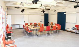 Møterom med oransje stoler, mikrofoner på bordene, skjermer og tavler på veggene.