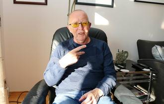 Eldre døvblind mann med gule fargefilterbriller sitter i sin godstol. Han viser med sin høyre hånd en v-håndform mot sofagruppen i stua.