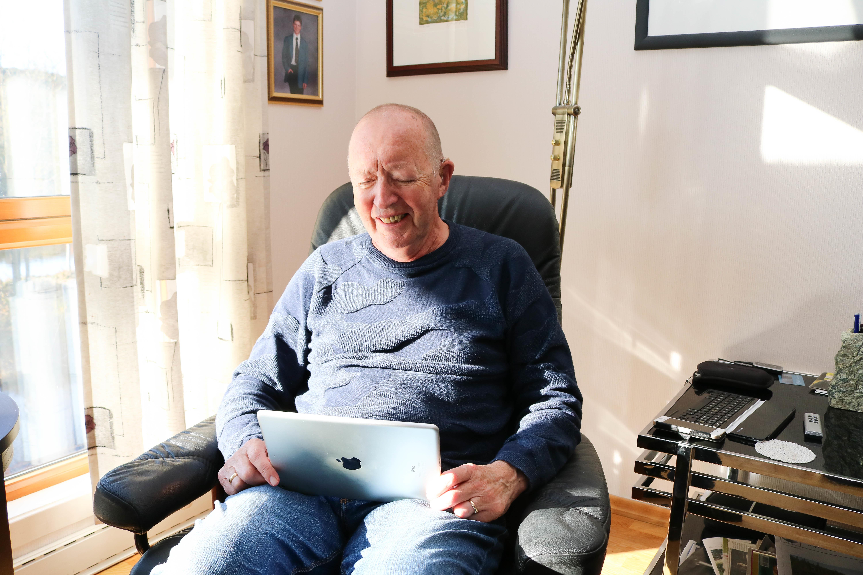 Eldre døvblind mann sitter i sin godstol og ser på sin Ipad. Ettermiddagssol fra venstre.