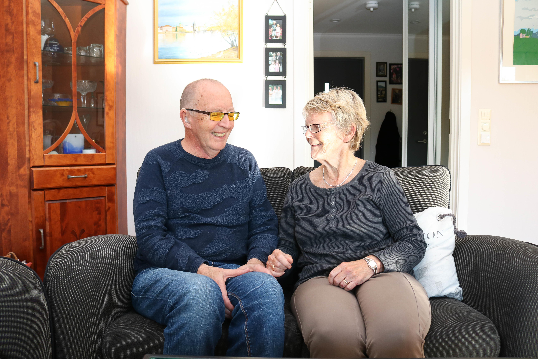 Eldre døvblind mann sitter tett med sin døve kone i en grå toseter. De smiler til hverandre.