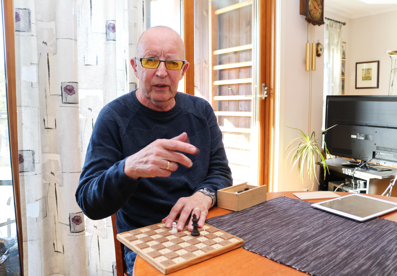 Eldre døvblind mann med gule fargefilterbriller sitter ved et spisebord, og viser fram et taktilt sjakkbrett.