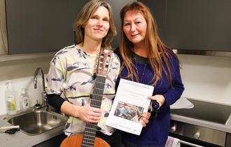 To kvinner står på et kjøkken og viser fram en prosjektrapport. Damen til venstre har lys bluse og holder en gitar, mens hun til venstre har på seg en lilla genser.