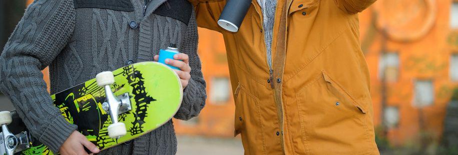 Bilde av to ungdommer med skateboard og sprayboks