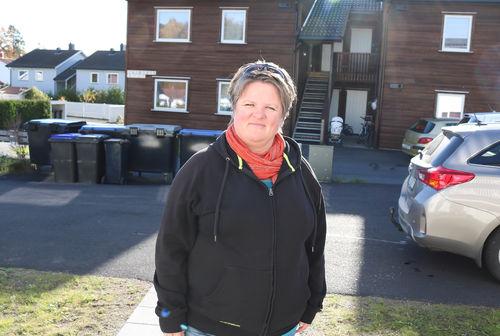 Døvblind kvinne står utenfor sitt hjem. Hun har på seg svart hettegenser og rødt sjal i halsen. Hun smiler i solen.