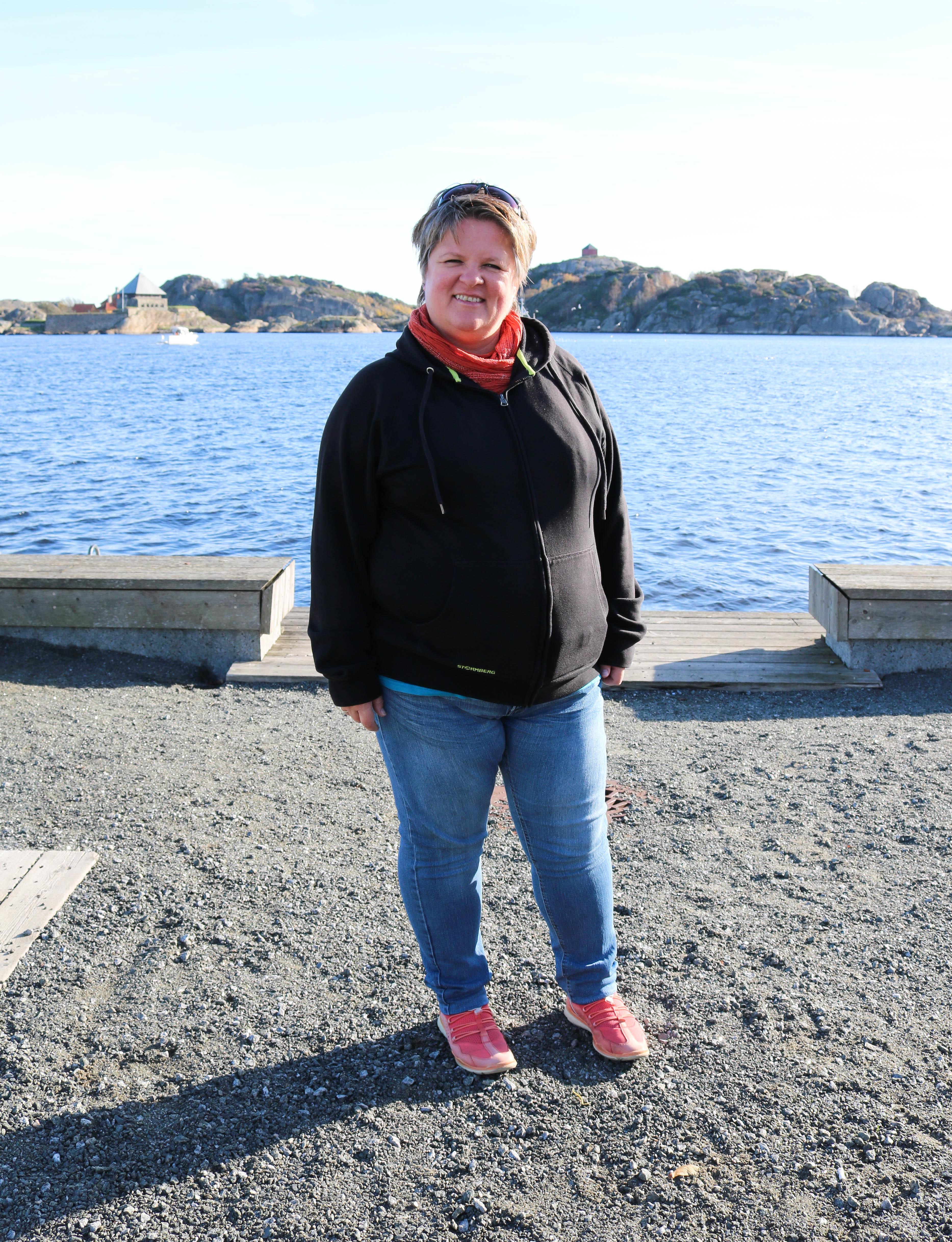 Døvblind kvinne står på havna i Stavern. Himmelen og sjøen bak henne er blå. Solen skinner på henne fra høyre side.
