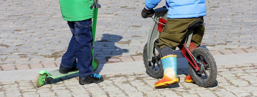 Illustrasjonsbilde av to gutter. Den ene har sparkesykkel, og den andre har sykkel.