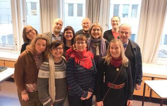 Gruppebilde av elleve smilende personer, stående foran en rekke med avlange vinduer, i et undervisningsrom. Sju av dem er kvinner, mens resten er menn.
