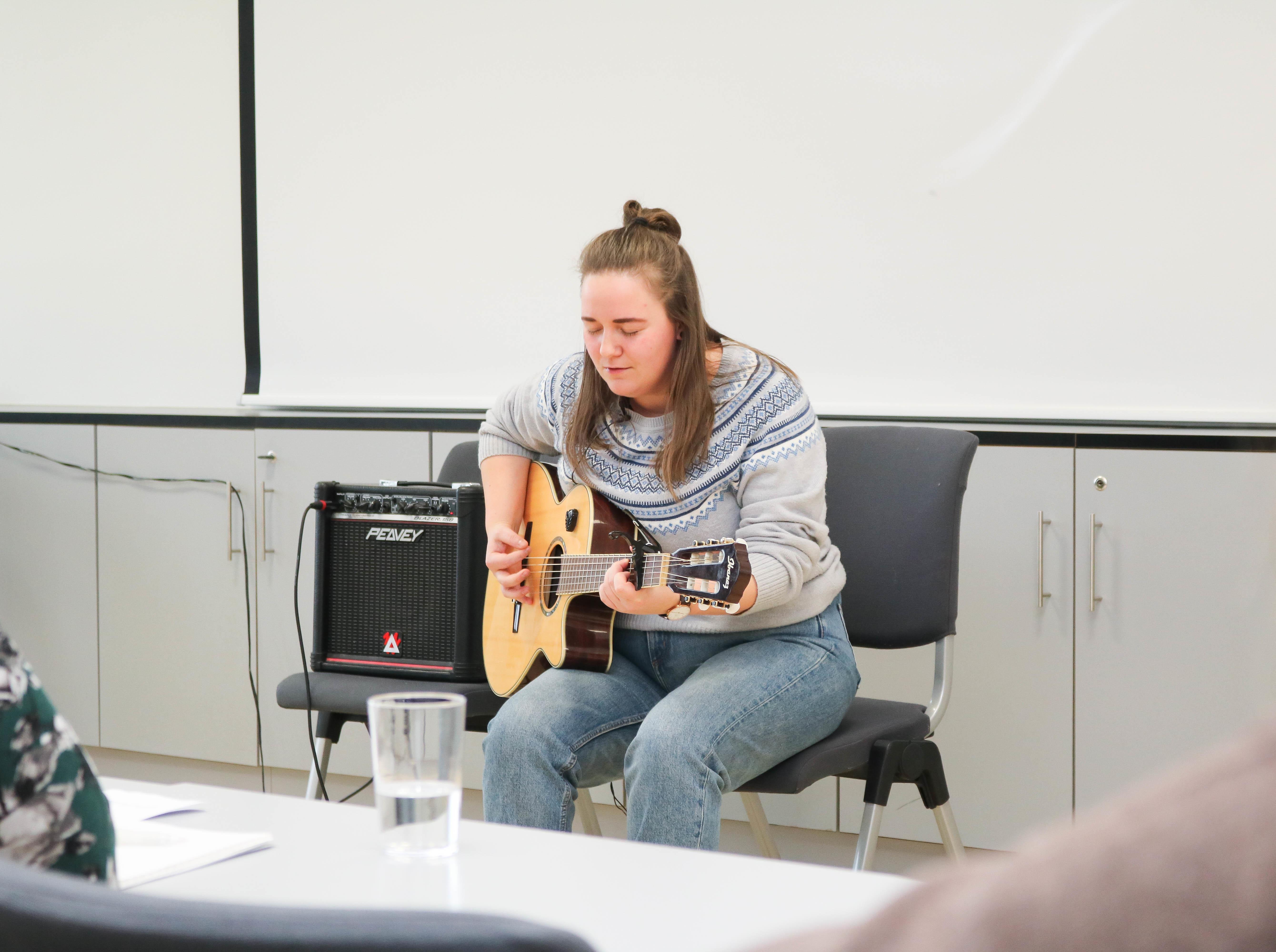 En kvinne med grå genser sitter på en stol og spiller på en gitar mens hun synger med lukkede øyne.