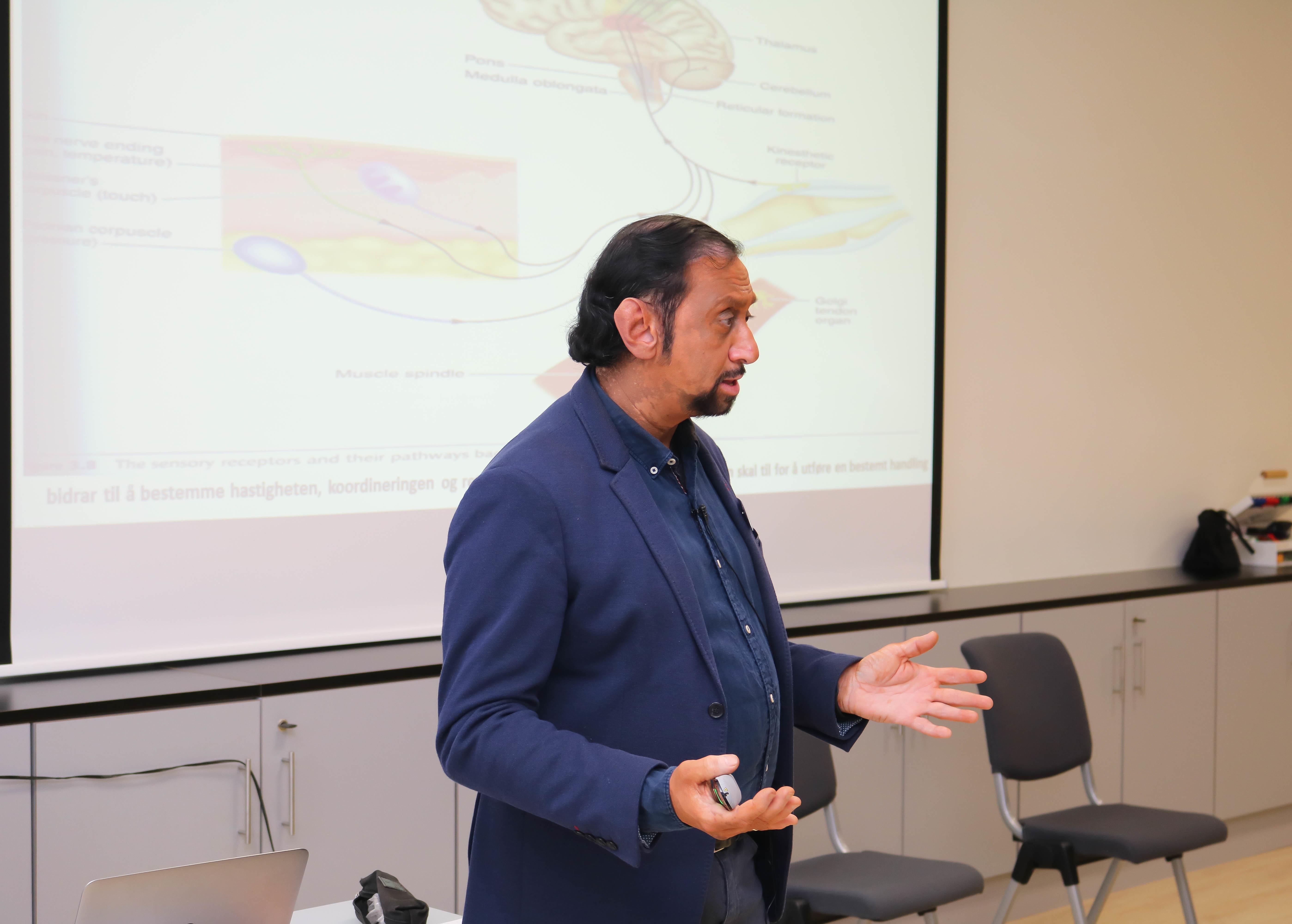 En mann holder hendene sine fram mens han holder et foredrag, i bakgrunnen sees en slide med tegninger av hjernen.