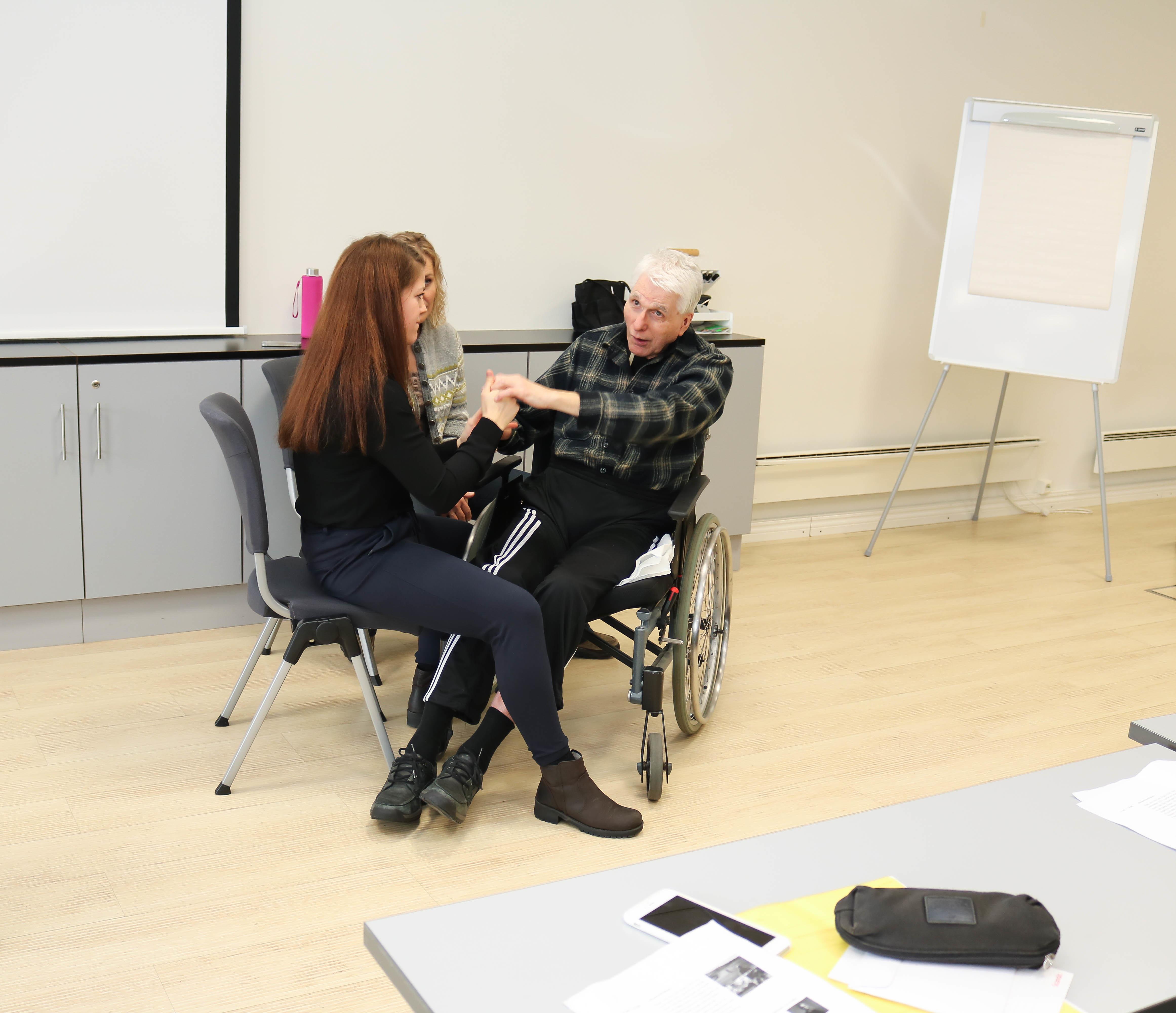 Døvblind, eldre mann i rullestol får hjelp at to kvinnelige ledsagere til å fortelle sin historie.