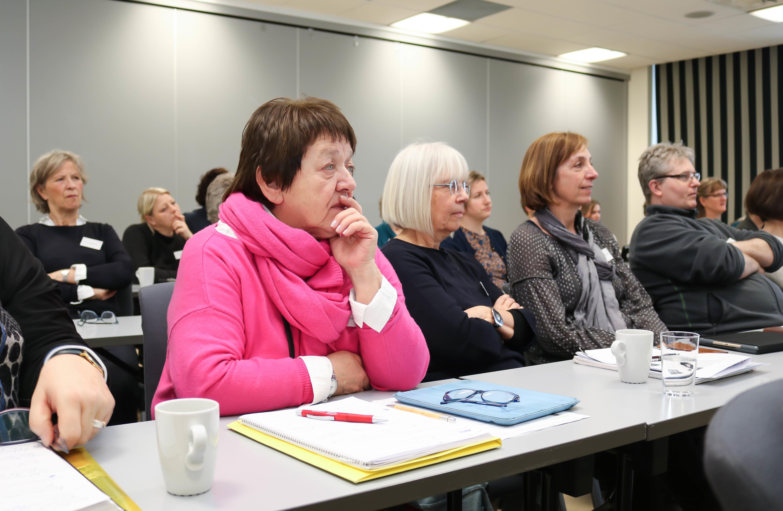 Rådgiver-deltakere som følger med på foredrag. I front sitter en kvinne med rosa genser og skjerf. Til høyre for henne to kvinner og en mann.