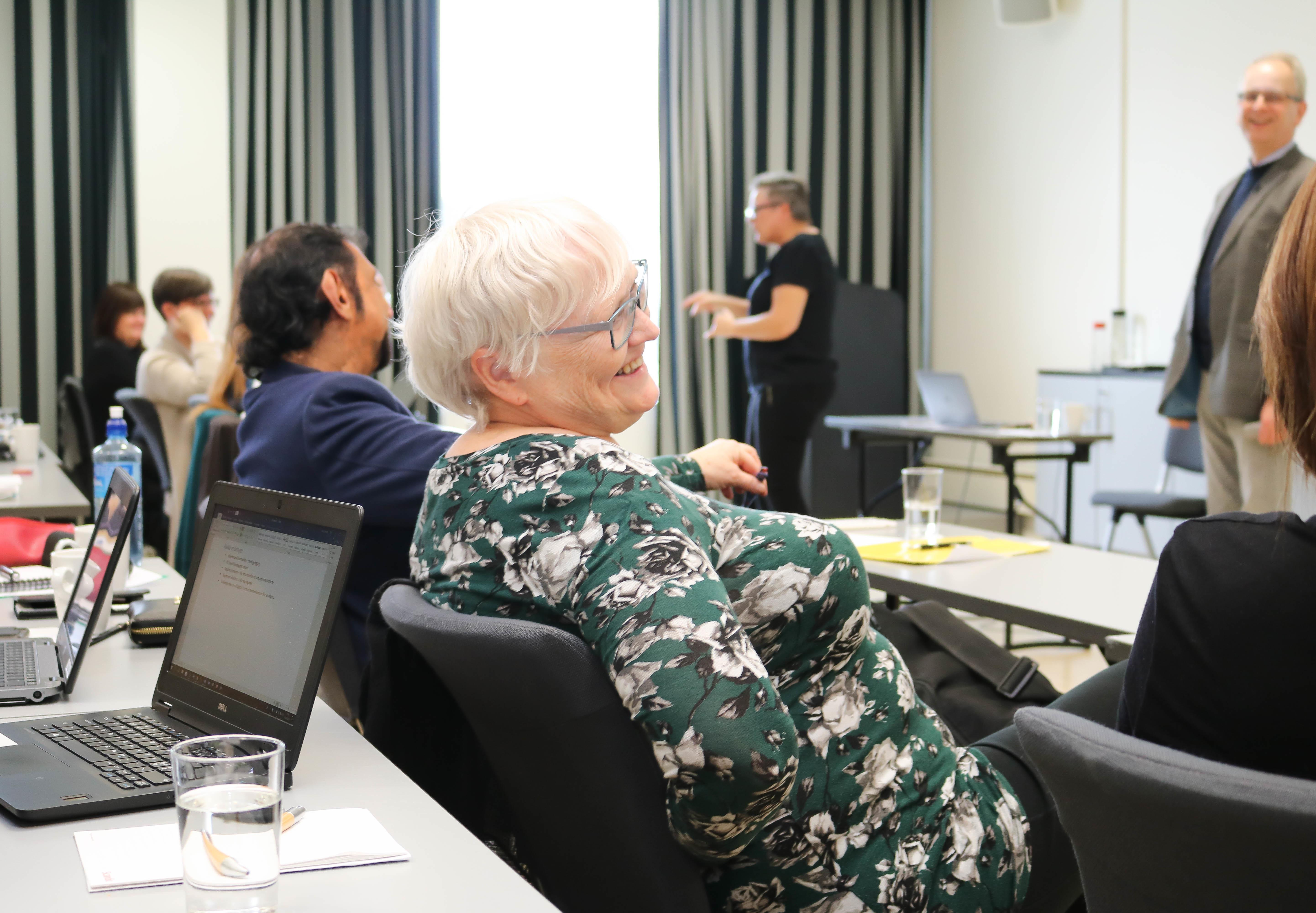 Kvinne med hvitt hår og briller smiler og lener seg tilbake på stolen sin, under foredrag.