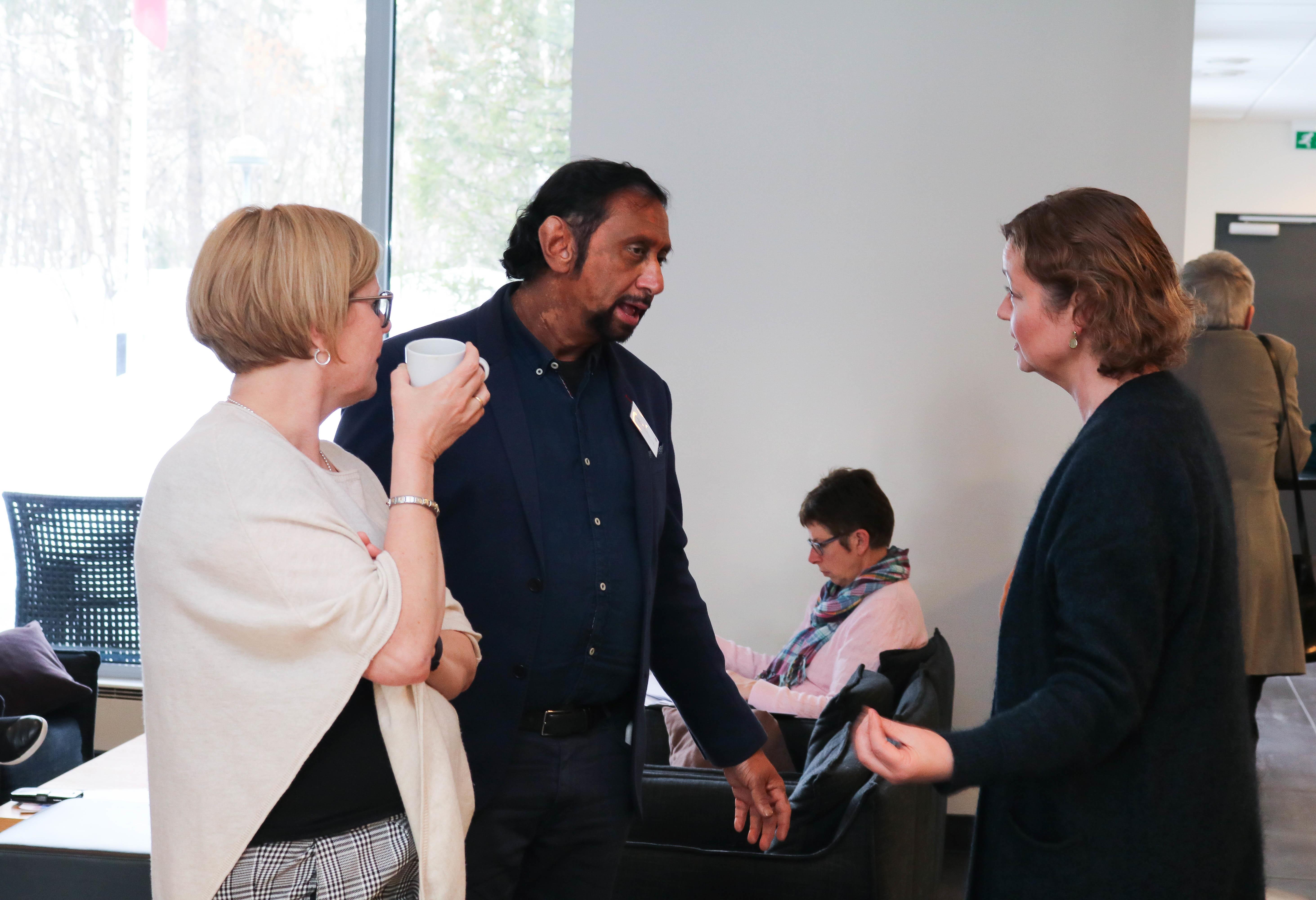 En mann og to kvinner diskuterer i en kaffepause.