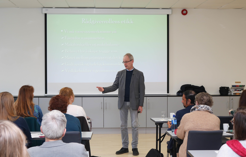 Mann med briller og kledd i grått holder foredrag for samlingsdeltakere.