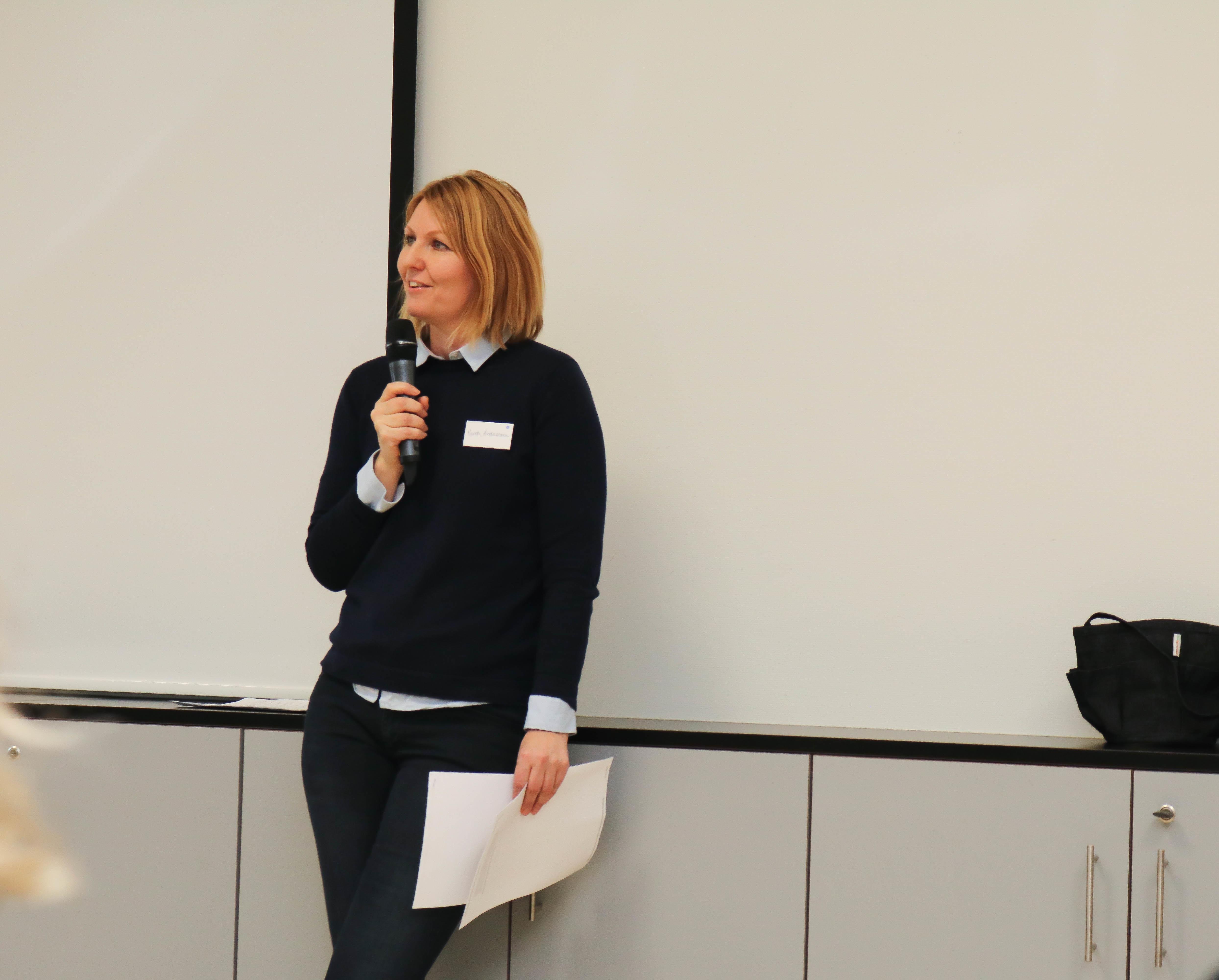 Kvinne kledd svart prater i en mikrofon og holder noen ark i sin venstre hånd.