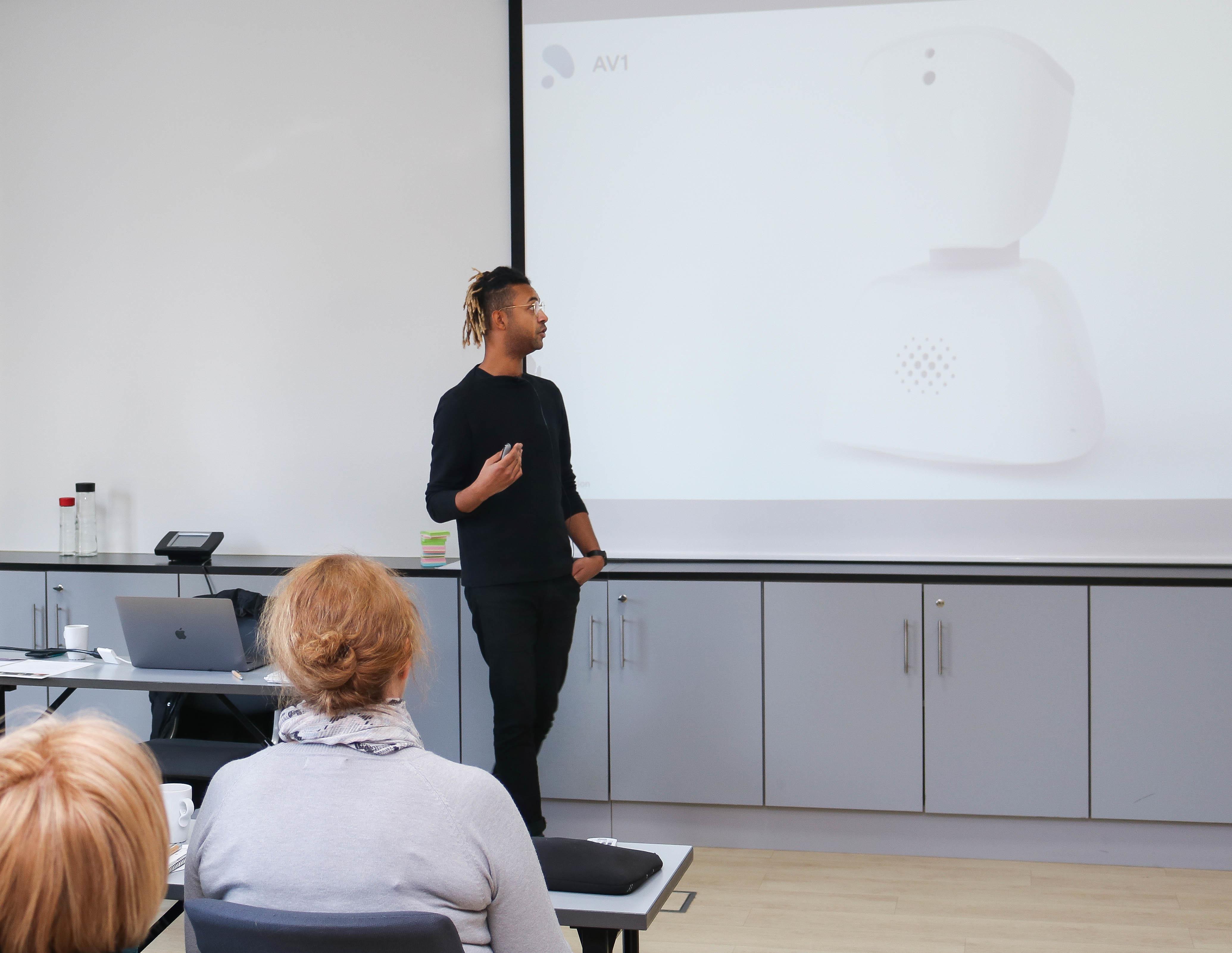 Mann kledd i svart holder foredrag mens han viser fram roboten A1 på Power Point.
