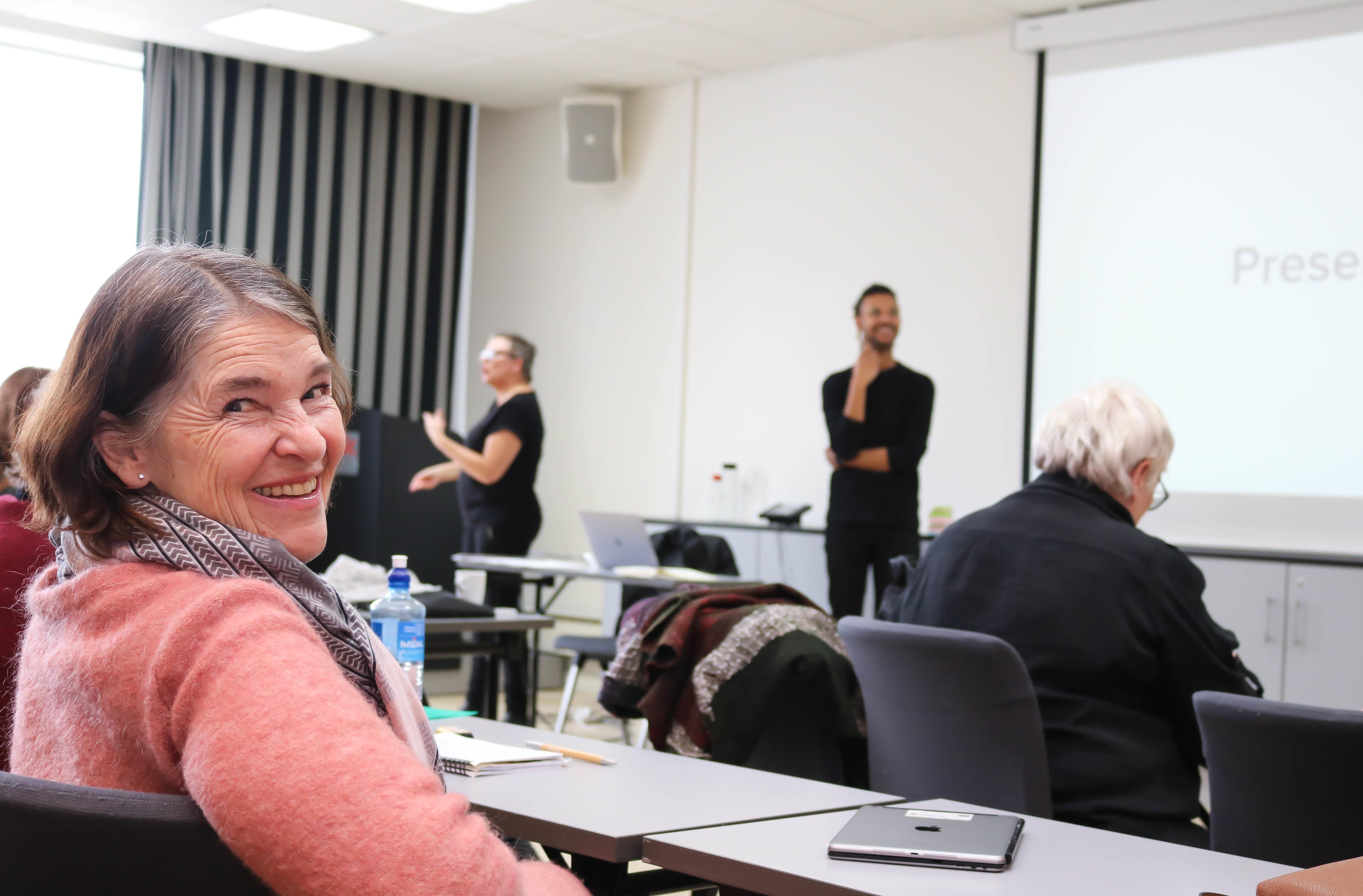 Kvinne ser inn i kamera, mens mann i bakgrunnen holder foredrag. Til venstre for ham står en kvinnelig tolk.