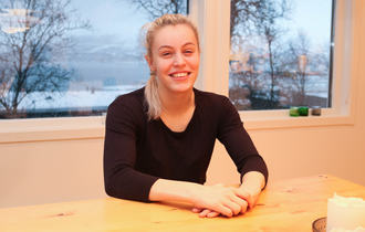 Ung smilende kvinne sitter med foldede hender ved enden av et kjøkkenbord.