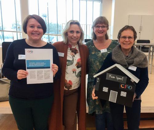 """Fire kvinner står tett samme og smiler. Hun ytterst til venstre holder på et ark med informasjon om CFD, men hun som står ytterst til høyre viser fram et """"CDF-hus"""" med påskriften """"Kom igjen!""""."""