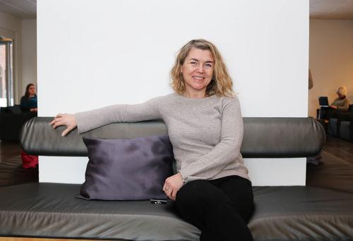 Lyshåret kvinne sitter i et mingleområde i en gråblank sofabenk. Hun smiler og ser rett i kamera.