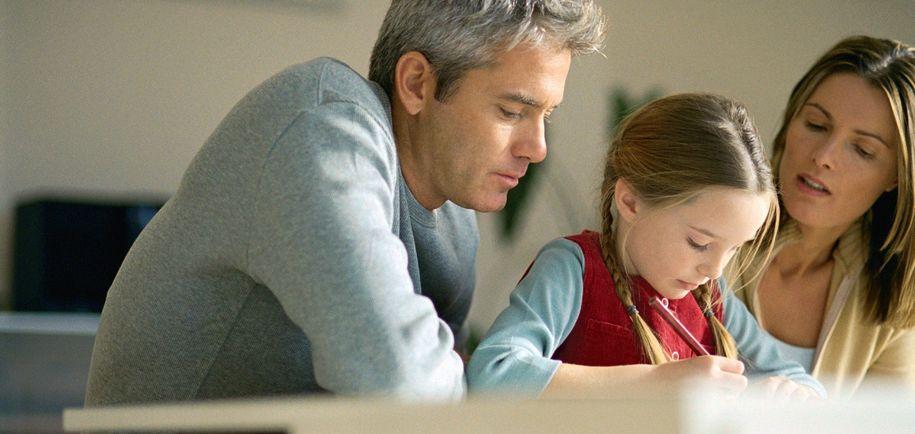Bilde av to voksne som sitter ved ei ung jente og leser lekser