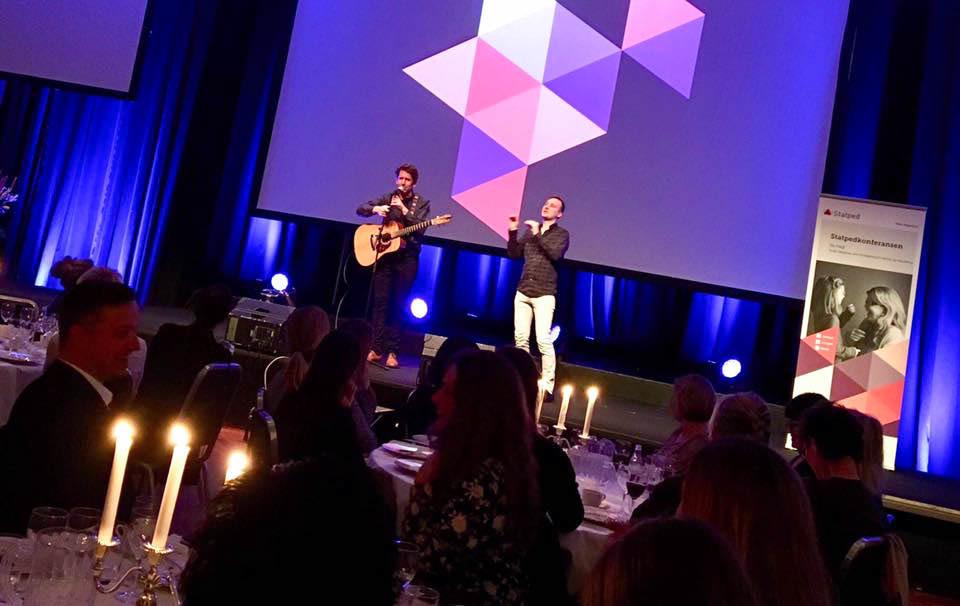 Musiker Odd Nordstoga synger med gitar rundt halsen. Til høyre for ham en døvetolk som tolker sangen.