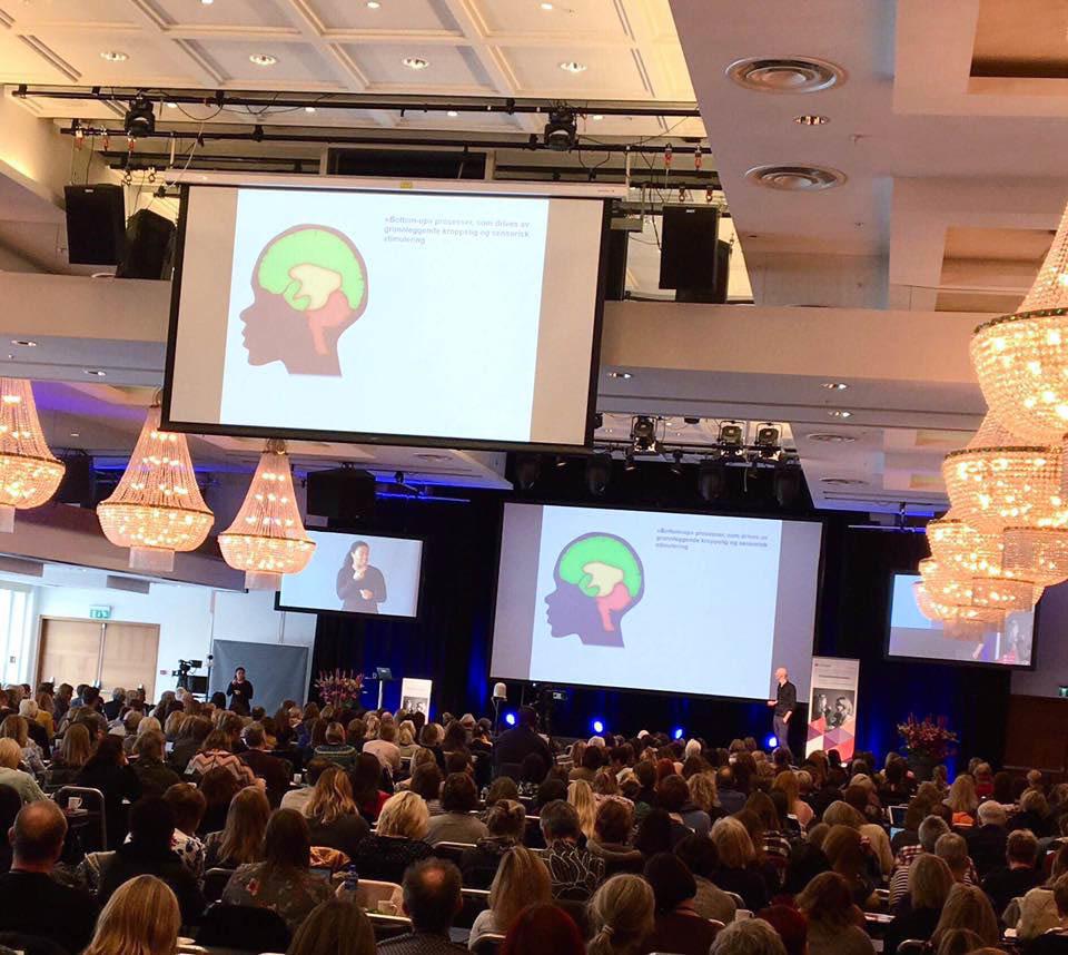 Konferansesal med masse mennesker. To skjermer i overkant viser en PowerPoint-illustrasjon av en hjerne.