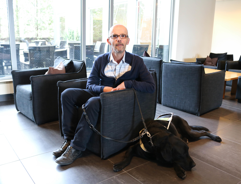 Mann med briller sitter i en blå stål. Han holder båndet til en svart førerhund som ligger på gulvet ved stolen.