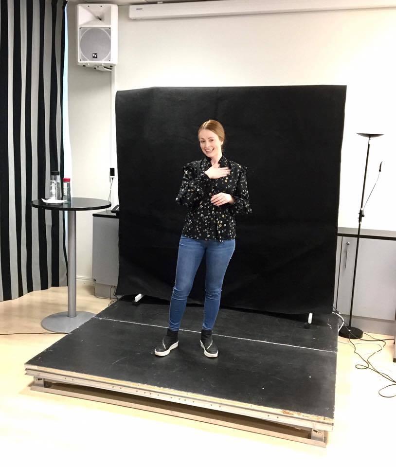 Kvinnelig foreleser og tegnspråkbruker står på en sort tolkescene holder sitt foredrag.