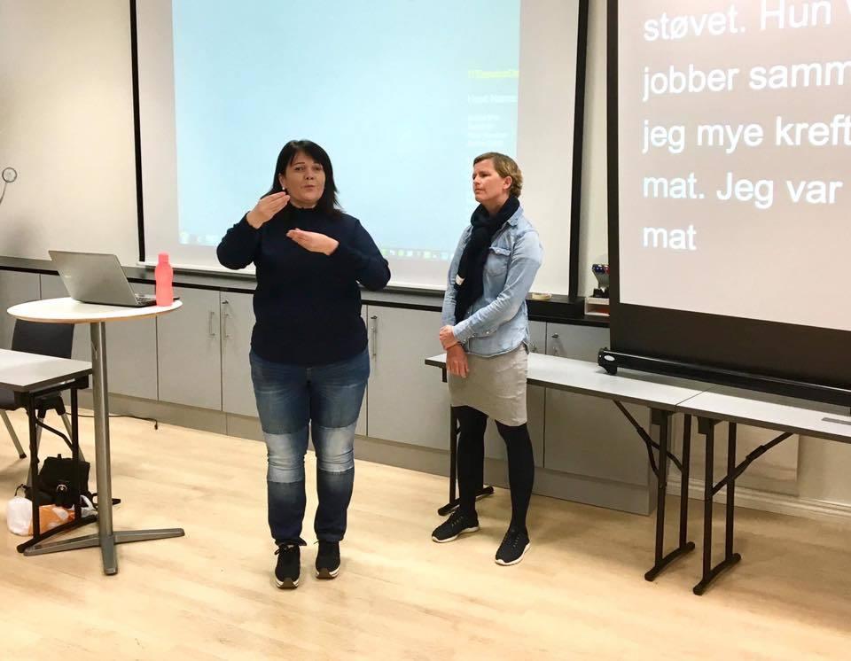 En kvinnelig foreleser og tegnspråkbruker med sort genser, ved hennes høyre side en kvinnelig tolk med lys dongeriskjorte og svart skjerf.