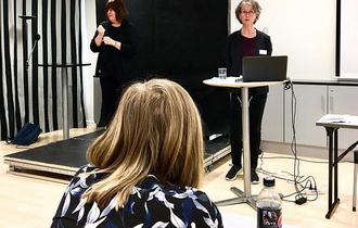 Kvinnelig foreleser og tolk på sort scene, sett bak en kvinnelig deltaker med mørkeblondt hår.