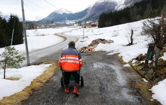 En mann kledd i oransje arbeidsjakke går nedover en innkjørsel med en trillevogn.