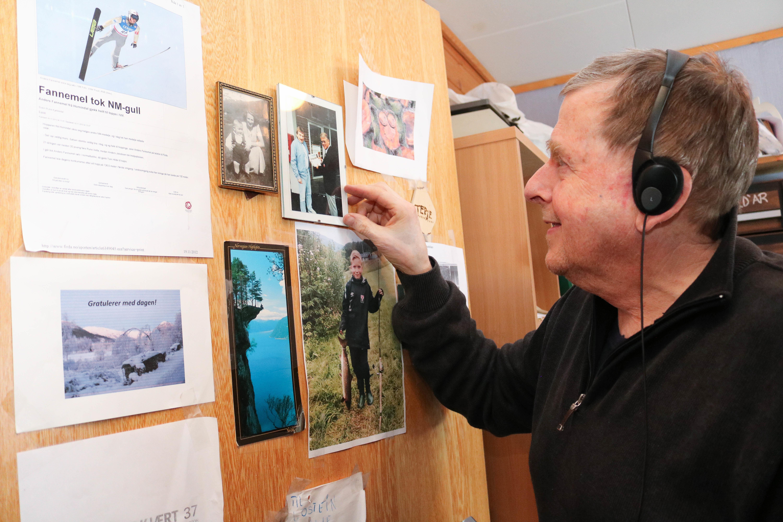 Eldre mann med headsett viser fram en del bilder og utklipp som henger på døra til et hjemmekontor.