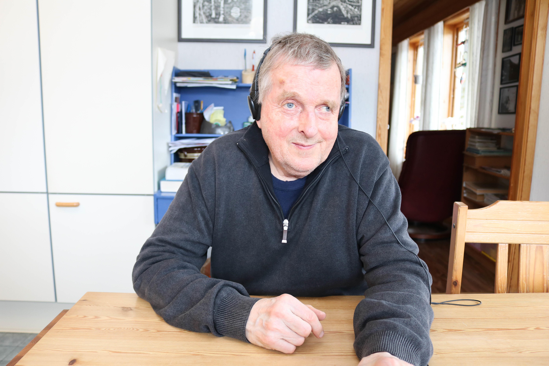 Mann med grått hår og svart headsett sitter ved et spisebord.