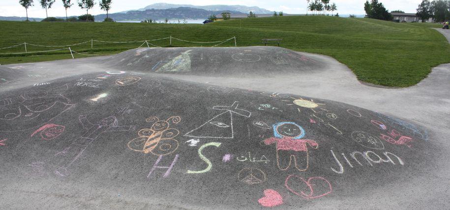 Bilde fra Midtsandtangen der barn har tegnet på asfalten med kritt