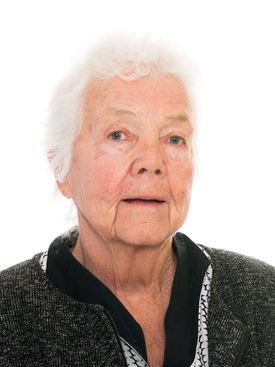 Portrettfoto av eldre kvinne. Hvitt, kort hår. Mørk jakke, med lysere skjorte under.