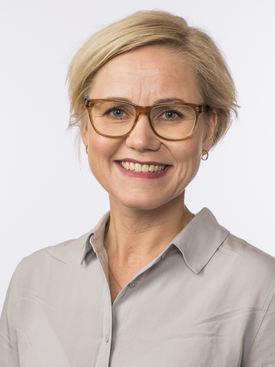 Portrettbilde av kvinne med halvlangt lyst og og røde briller. Hun har på seg en grå skjorte og hun smiler.