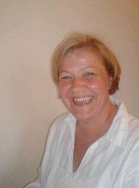 Portrettbilde. Lys, smilende kvinne med hvit skjorte.