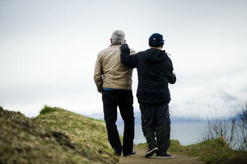Eldre mann ledsager yngre mann i fjæra med snødekte fjell i bakgrunn