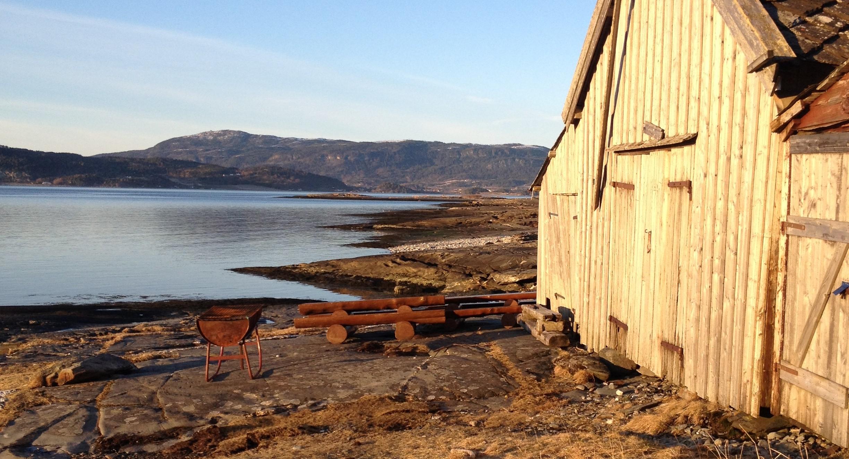 Bilde fra Flatholman friluftsområde med naust i sjøkanten