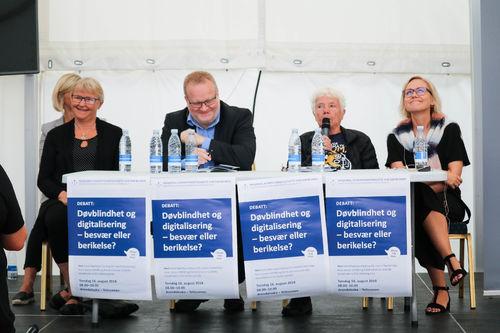 En mann og tre kvinner i en panel-diskusjon. En rekke med plakater henger foran dem og har overskriften: Døvblindhet og digitalisering, besvær eller berikelse?