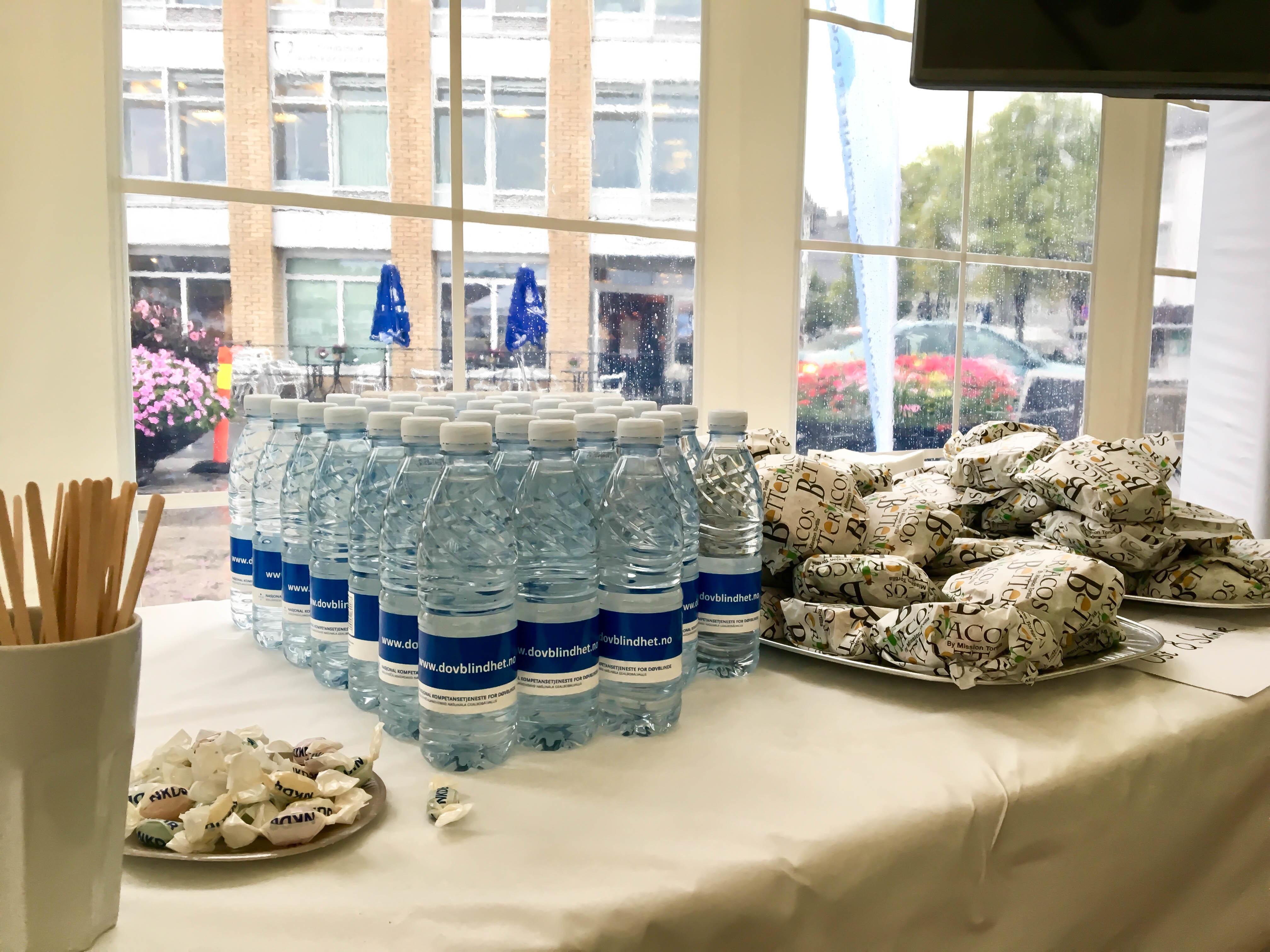 En samling med flaskevann, innpakkete sandwicher og drops på et bord med hvit duk.