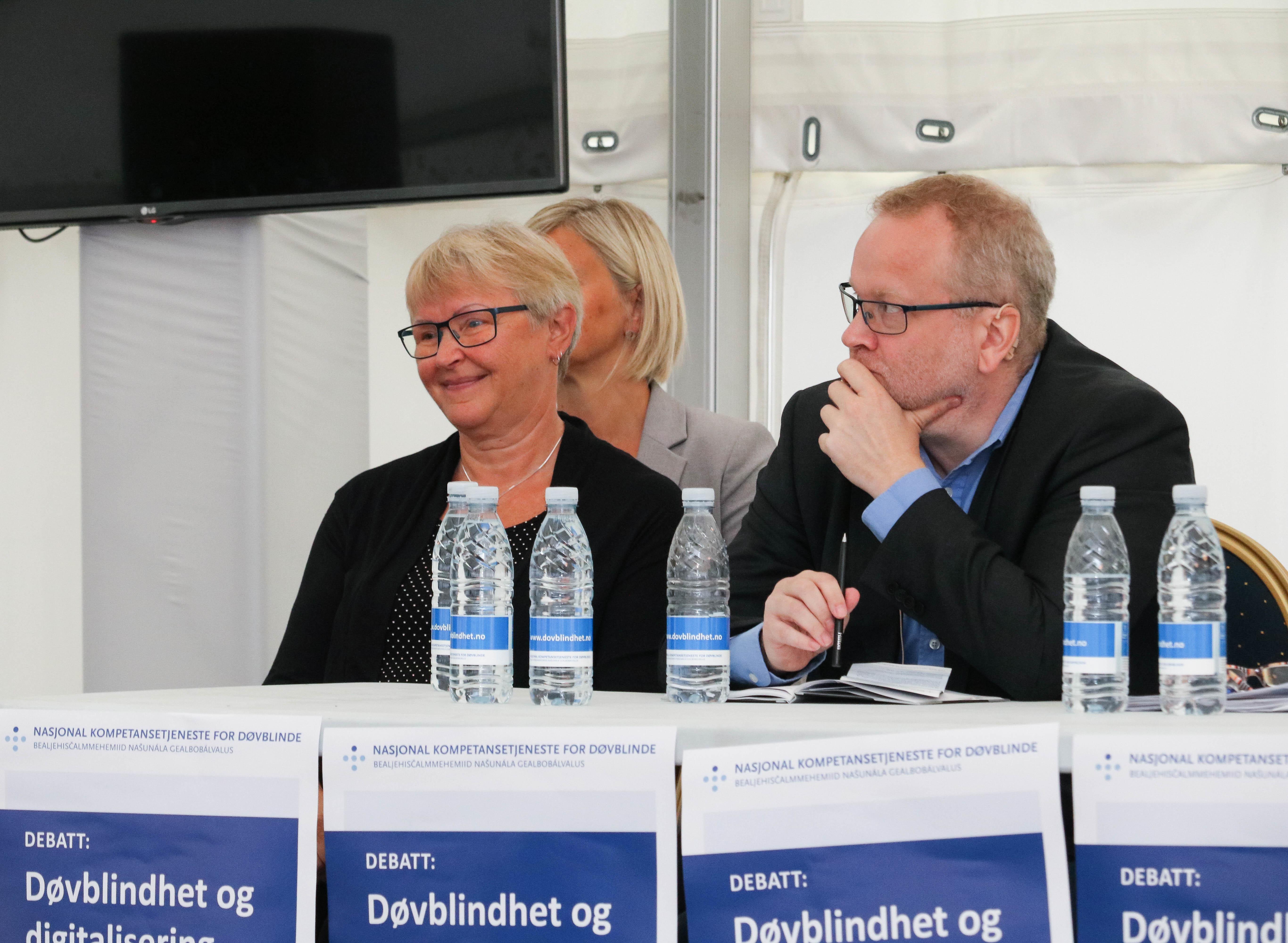 Paneldiskusjon. Tre personer, en kvinne til venstre med en tolk bak seg. Mann til høyre.