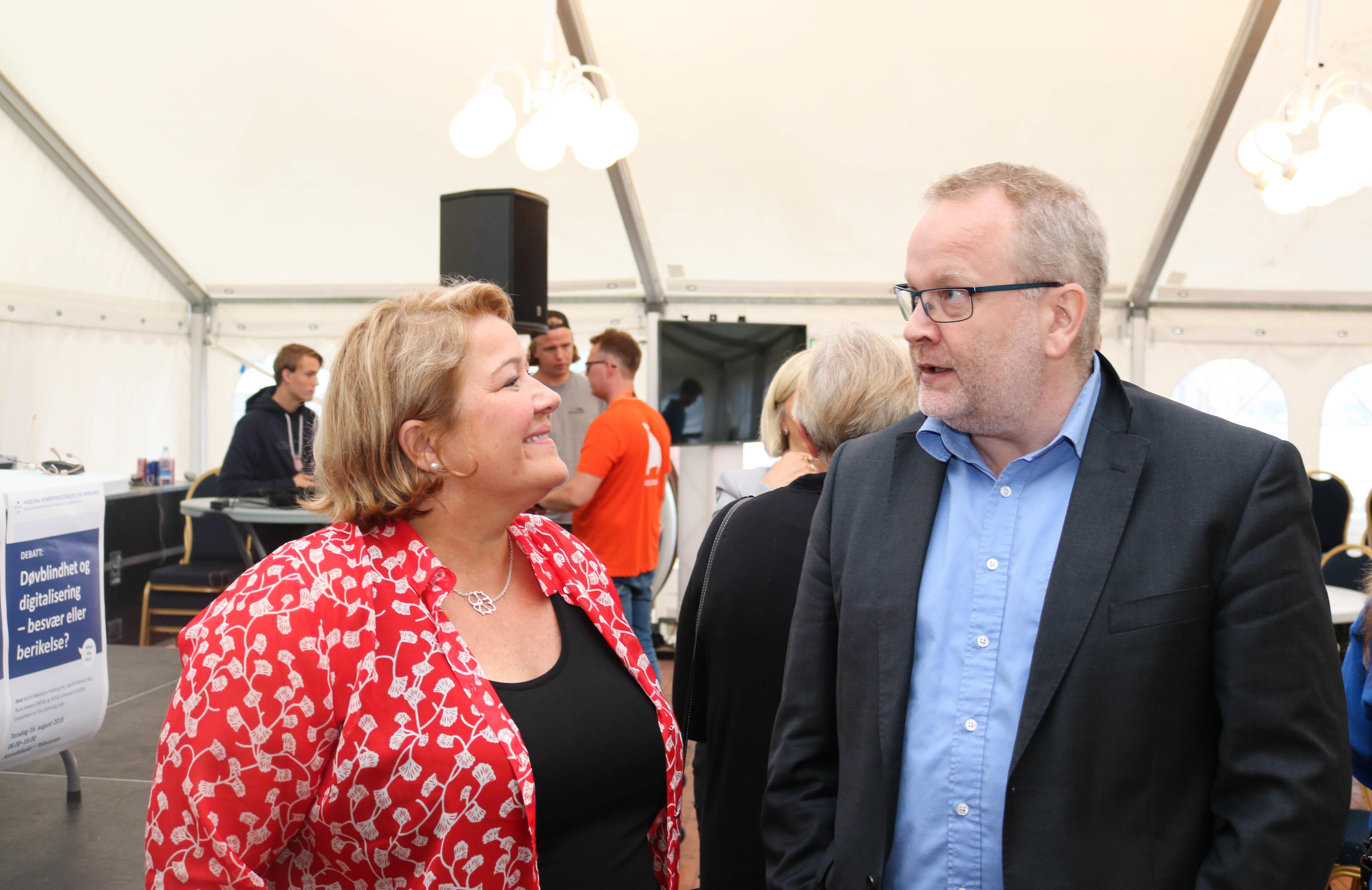 Kvinne og mann prater sammen. Hun er rødkledd, mens han har blå skjorte under svart dressjakke.