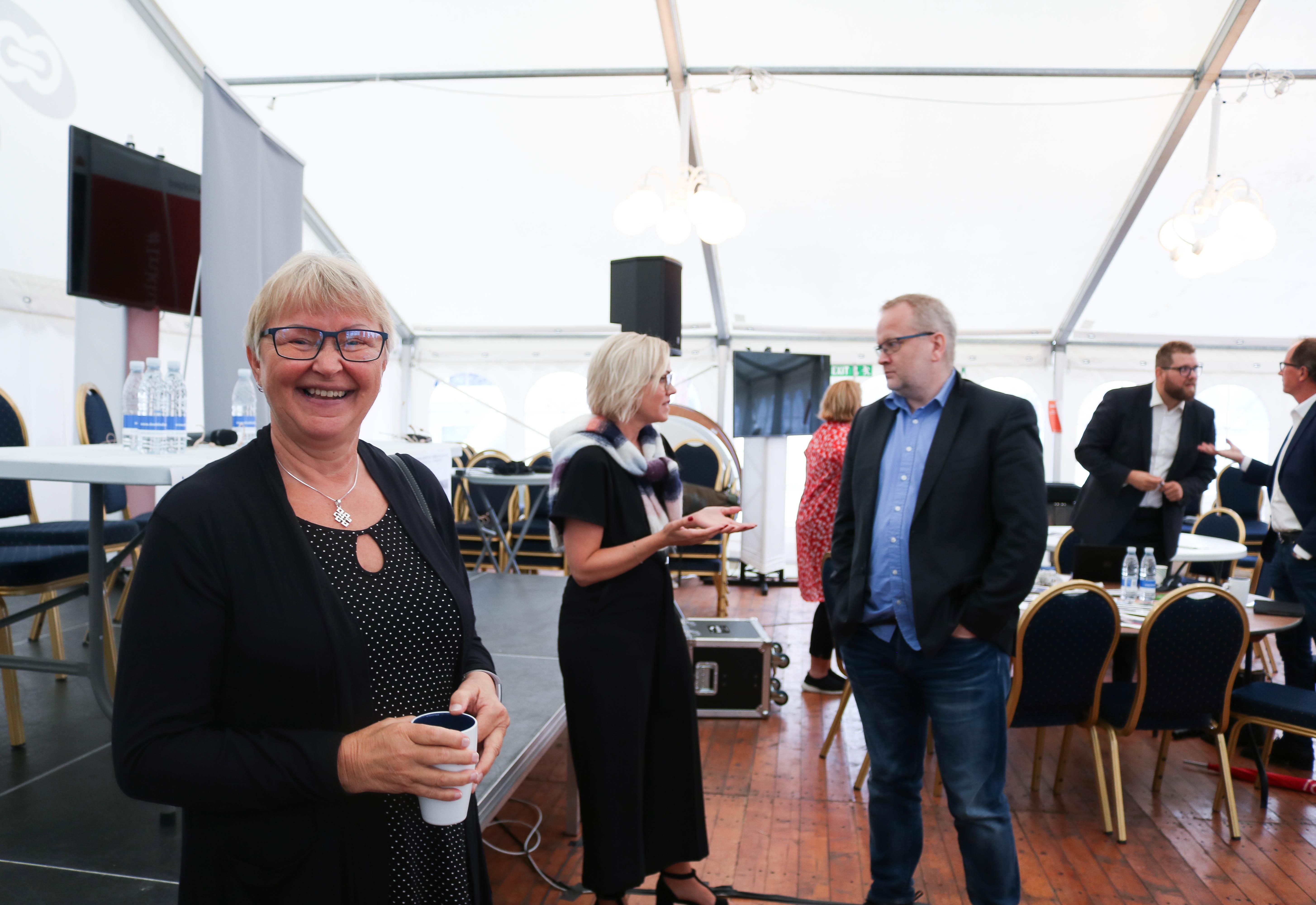 Flere personer står og prater med hverandre i en teltscene. Kvinne nærmest til venstre, har grått hår og kledd i svar. Hun ser i kamera og smiler.