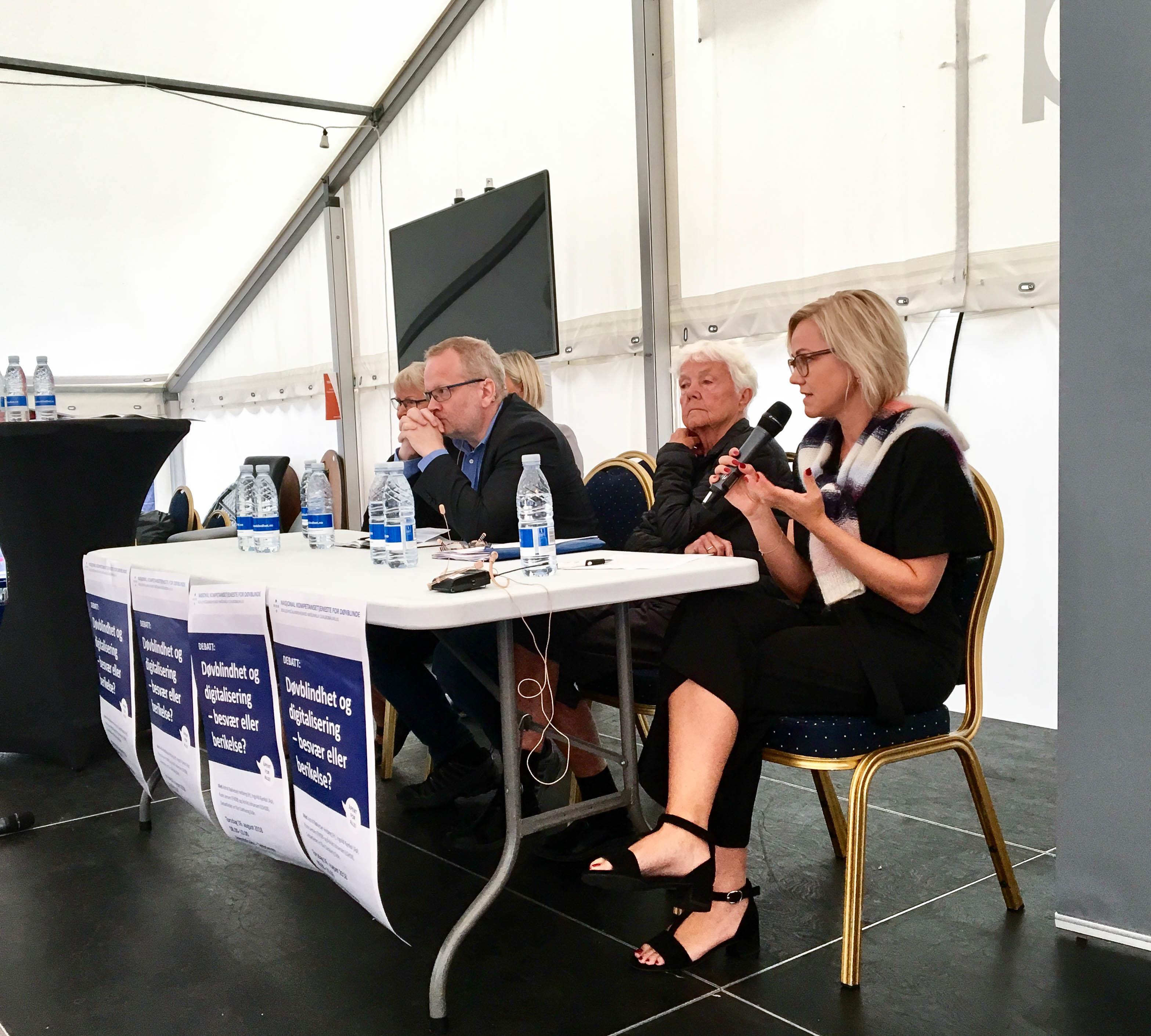 Debatt-scene med fire debattanter. Nærmest kvinne som prater i mikrofon.