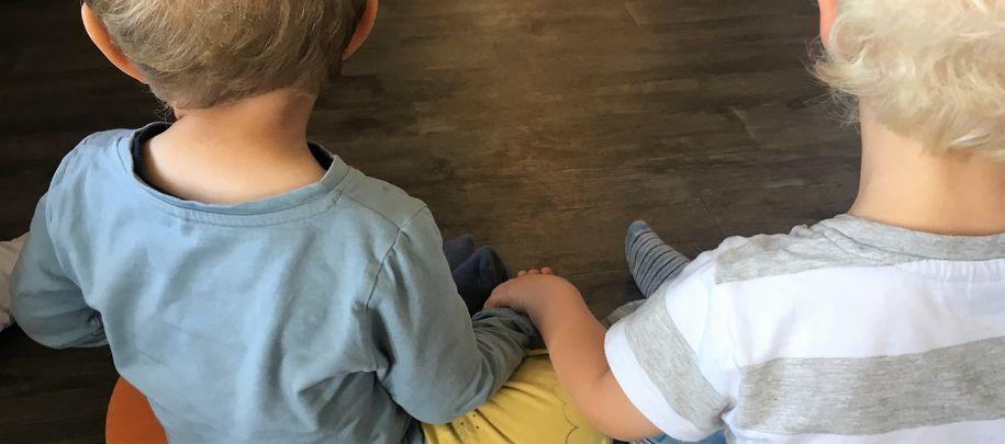 Bilde av to barn som sitter med ryggen til, og holder hender