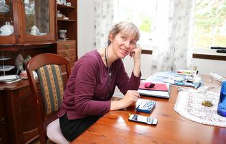 Kvinne med lilla genser i spisestue. Hun bruker sin mobil ved hjelp av headset og leselist. Hun hviler hodet på venstre hånd og smiler mot kamera.