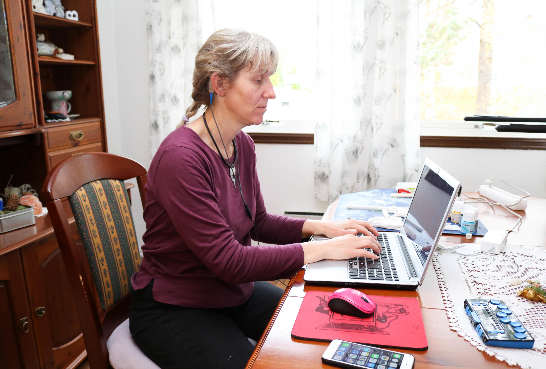 Spisestue. Kvinne i lilla genser sitter ved bordet og skriver på en laptop.