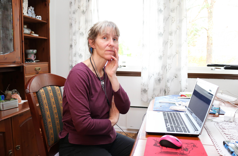 Spisestue. Kvinne i lilla genser sitter ved sin laptop og ser i kamera, hun holder venstre hånd mot kinnet sitt.